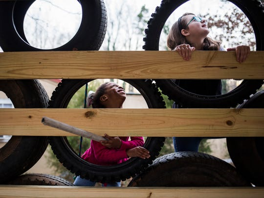 Delainey Vernon, 7, and her sister Emma Grace Vernon, 9,  climb up a tire wall Thursday to get to the treehouse at their home in Starr.