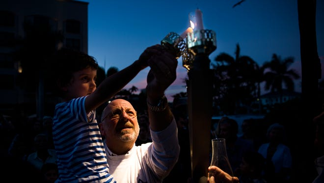 Rabbi Ammos Chorny, of Beth Tikvah in North Naples, helps Arthur Lipo, 4, light the second candle of the menorah at the Community Chanukah Celebration at Mercato in North Naples on Monday, Dec. 26, 2016. The event featured a latke eating contest, music and candle lighting.