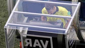 Referee Matt Conger from New Zealand watches the Video Assistant Referee system, known as VAR, during the Group D match between Nigeria and Iceland in the World Cup.