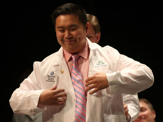 Ryan Huynh is coated during the Medical College of Wisconsin Central Wisconsin White Coat Ceremony at UW Marathon County, in Wausau, Wisconsin, July 7, 2016.