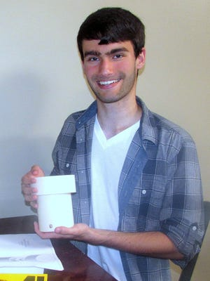 Jacob Zelko holds up a prototype of a water-filtration system he designed as a Corning Community College engineering student.