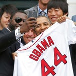 Boston Red Sox designated hitter David Ortiz (left) takes a selfie while presenting President Barack Obama (right) with a Red Sox jersey at a ceremony honoring the 2013 World Series champion Red Sox on the South Lawn at The White House.