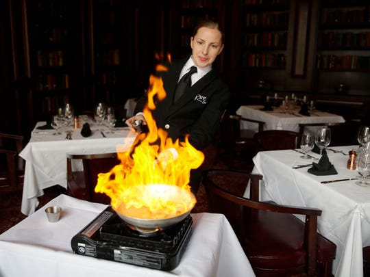 Fire ignites after a banana liquor and rum is poured on a bananas Foster desert by Erika Dralle, a dining room captain, that''s prepared table side.