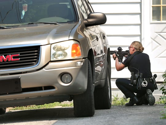 IMPD Officer Jennifer Asher draws her AR-15 assault rifle as she and other IMPD officers backed up the Marion County Sheriff Department serving a warrant on a suspect for possession of a firearm, strangulation, confinement and allegedly putting a gun to his sisters head during her shift on Thursday, August 13, 2015.