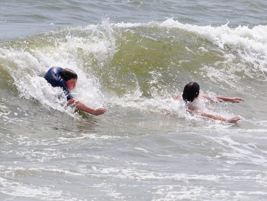 In this file photos, beachgoers body surf the waves
