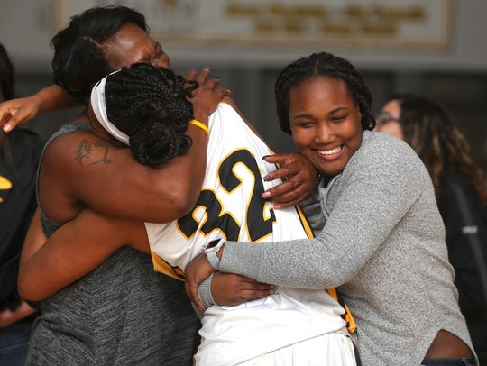 From left: Barbara Lawson, hugs her daughters, Justyce Cooper and Alex Cooper, after a 67-63 Enterprise win over Oakland on Wednesday.