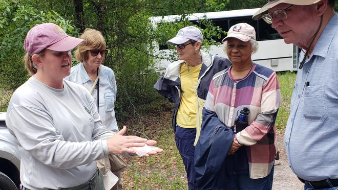 Archaeologist Thadra Stanton from the Southeast Archeological Center shows participants an artifact found at the Byrd Hammock archaeological site, in Wakulla County, where two Native American villages were located, between 200 and 900 AD.