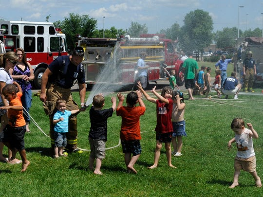 Children cool off in the spray from a fire hose during