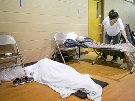 Summer Jett, 21, prepares her cot to sleep at Safe To Sleep, an overnight shelter for homeless women at Pathways United Methodist, as another woman sleeps on a mat on the floor on Tuesday, April 24, 2018.