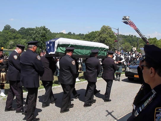 New York City police officers carry in the flag draped