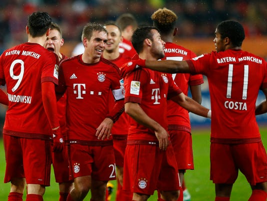 Bayern's Robert Lewandowski, left, celebrates with teammates after scoring his side's second goal during the German first division Bundesliga soccer match between FC Augsburg and FC Bayern Munich at the WWK Arena in Augsburg, Germany, Sunday, Feb. 14, 2016. (AP Photo/Matthias Schrader)