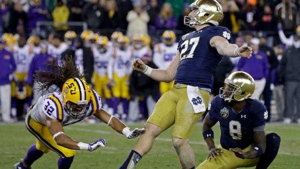 Notre Dame's Kyle Brindza (27) watches his 32-yard field goal that gave Notre Dame a 31-28 win over LSU as time ran out in the Music City Bowl NCAA college football game Tuesday, Dec. 30, 2014, in Nashville, Tenn. Holding for Brindza is Malik Zaire (8) and trying to block the kick is LSU cornerback Jalen Collins (32). (AP Photo/Mark Humphrey)