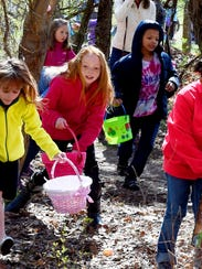 Egg hunters move from a trail into the woods as they