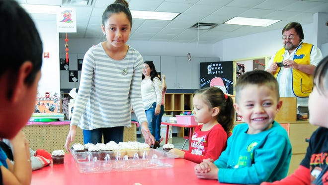 Lillyanna Martinez, 10 hands out cupcakes to Jardin de los Niños students on Thursday. Martinez decided to give gifts to needy children instead of receiving birthday gifts of her own this year.
