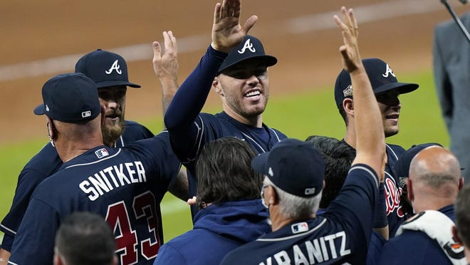 The Atlanta Braves' Freddie Freeman, center, celebrates after defeating the Miami Marlins in Game 3 of a National League Division Series on Thursday in Houston.