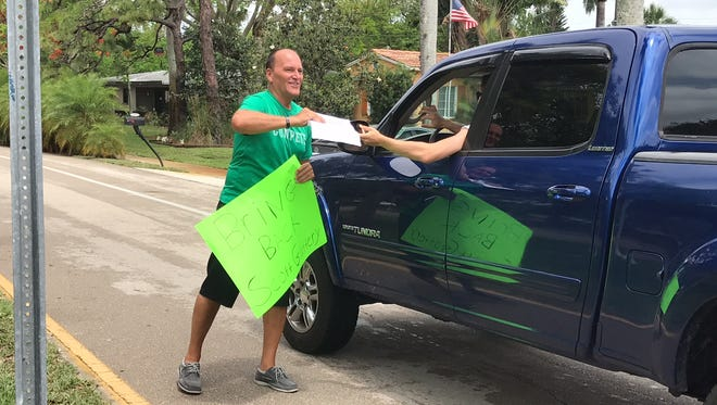 Sean Shores, father of a Fort Myers High school student-athlete, collected signatures in support of the school's basketball coach, Scott Guttery, in front of the school on Thursday.