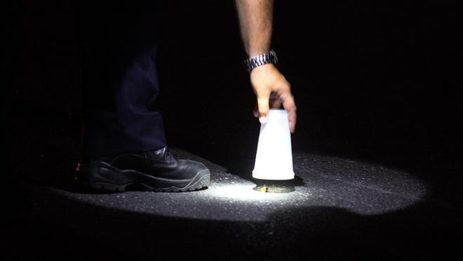 A police officer lifts a cup off a shell casing on Coleman Avenue in Long Branch Wednesday evening, July 22, 2015, where a multiple shooting allegedly occurred.