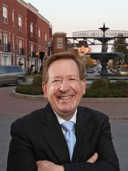 Carmel Mayor Jim Brainard stands in front of one of Carmel's famous roundabouts at the entrance to the city's Arts & Design District.