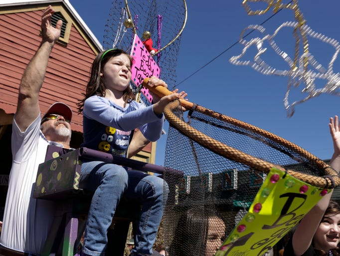 Abigail Pitre holds a basket to catch beads during