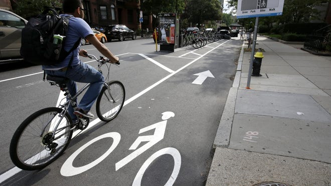 A cyclist enters a bike lane that is routed between parked cars and the sidewalk in Boston. Cities around the world are increasingly changing bike lanes to make them safer.