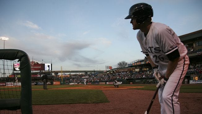 Louisville's Dan Johnson applies pine tar to his bat while on deck as the Bats play the Toledo Mud Hens on April 11.