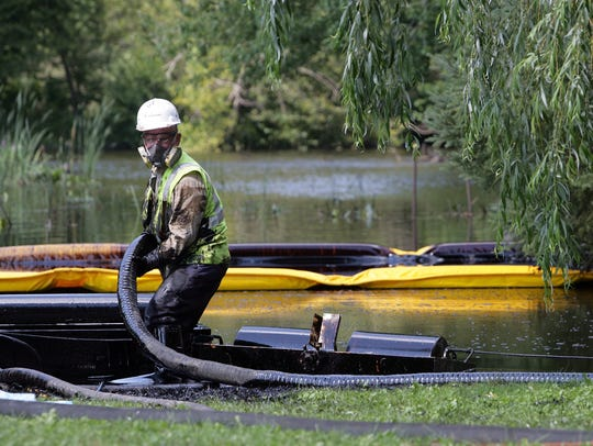 Workers from Enbridge skim oil off the surface of the