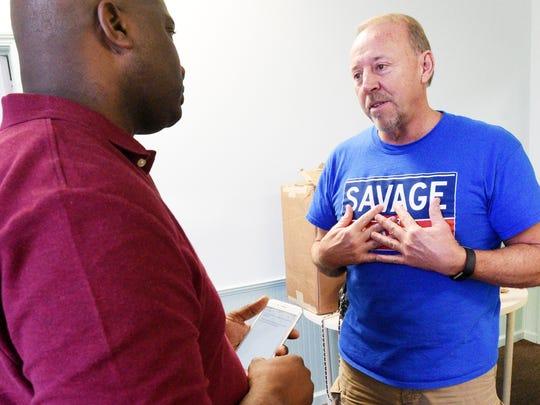 Eric Richardson, left, asks Lee  Savage, who is running