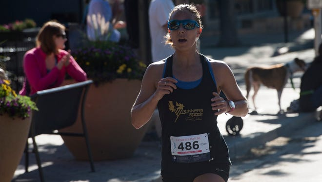 Heather Utrata is the first female runner to cross the finish line during the Father's Day 5K in Old Town on Sunday, June 18, 2017.