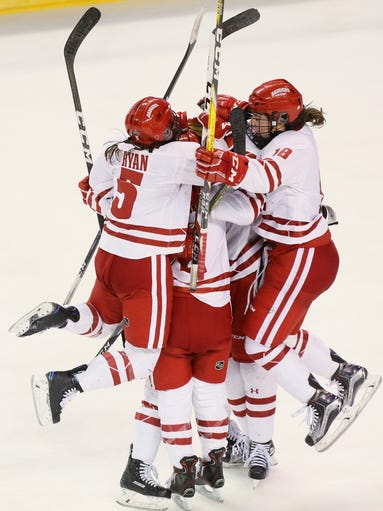 Wisconsin players celebrate around defender Mellissa