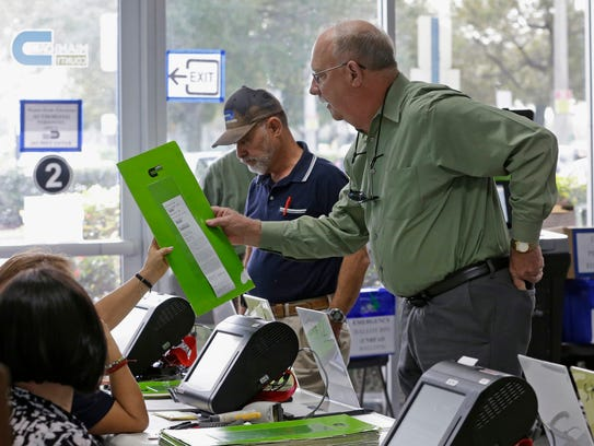 A voter receives his ballot as he prepares to cast