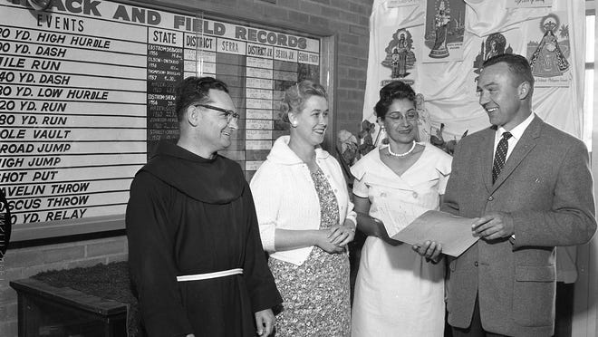 A group of people are seen during a dinner at Serra Catholic High School in front of the track and field record board.