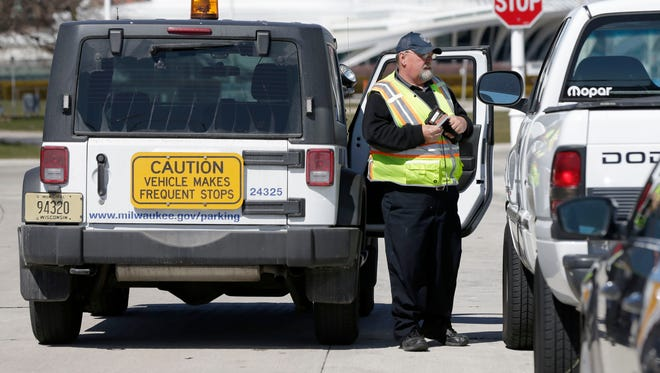 A City of Milwaukee parking attendant gives a vehicle a ticket parked on North Harbor Drive this year.