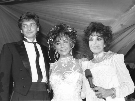 Carol Bayer Sager, right, Elizabeth Taylor, and Barry Manilow attend a fundraiser in Los Angeles, Ca. on July 25, 1986. The benefit is for the American Foundation for AIDS research. (AP Photo/Jacobs)