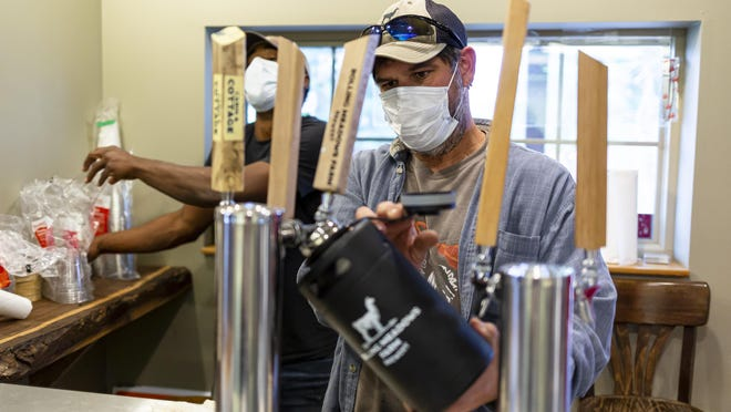 Jeff Medley, center, of Rolling Meadows Brewery, and Deion Corley, head brewer, fill customer orders of the brewery's farm-to-table beer from a section of their production facility that was converted to curbside ordering because of the COVID-19 pandemic at Rolling Meadows Farm Brewery, Friday, November 20, 2020, in Cantrall, Ill. Rolling Meadows Brewery, which was started by Caren Trudeau and her son, Chris Trudeau, in 2011 will cease production of their farm-to-table beer because of issues involving the COVID-19 pandemic.