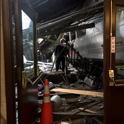 A NJ Transit train seen through the wreckage after
