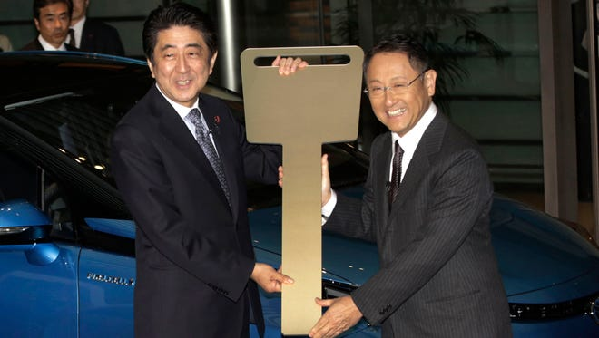 Japanese Prime Minister Shinzo Abe, left, receives a commemorative key from Toyota President and CEO Akio Toyoda, right, in front of Toyota's new commercial fuel cell vehicle during a ceremonial test drive at the prime minister's office in Tokyo in January 2015.