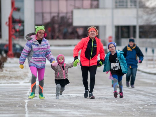Claire Bonner, from left, 11, of Marysville, holds hands with Aria Kinney, 3, of Port Huron, Bernadette Malooley, and Symone Bonner 6, of Marysville, as they approach the finish line Sunday, Jan. 29, during the PoHo Hot Cocoa Run in Port Huron.