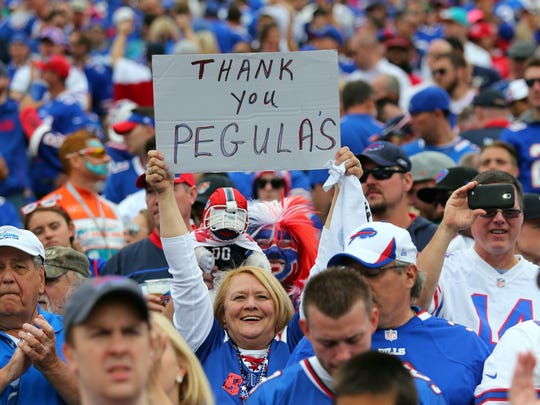 A fan holds a sign thanking then-prospective Buffalo Bills owners Terry and Kim Pegula on Sept. 14, 2014.
