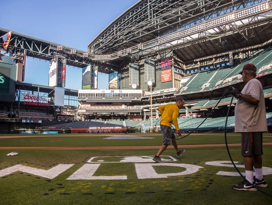 Brian Johnson paints the NLDS logo onto the field on