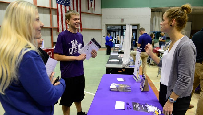 From right, Cheryl Logan, assistant director of admissions at Ashland University, talks with Fremont Ross junior Collin Heberling, his brother Andrew, 11, and mom Jennifer Ball at  a college fair at Terra State Community College Monday night.