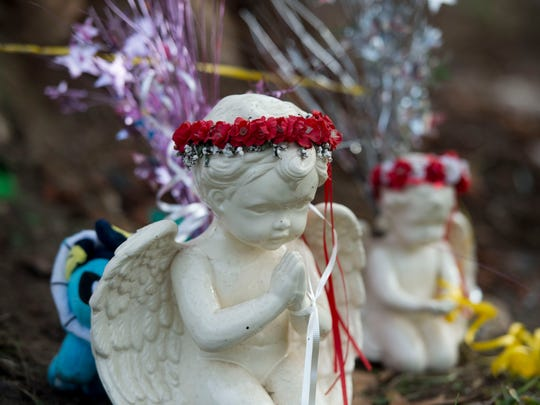 2_Angel statues sit among flowers and balloons at the