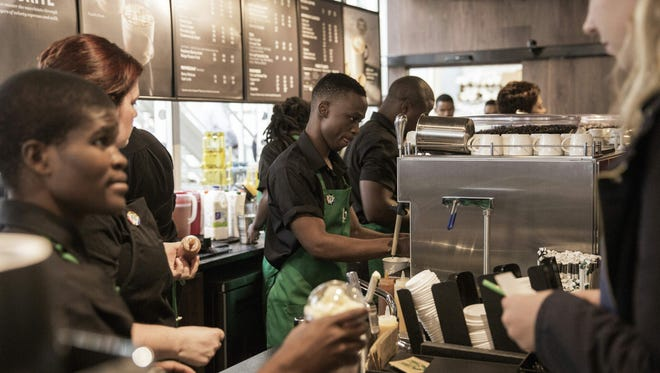 Starbucks employees serve customers during the official opening of South Africa's first Starbucks store, also the US coffeehouse chain's first store in Sub-Saharan Africa, in Johannesburg on April 21, 2016.