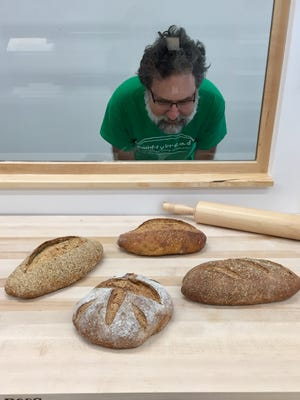 Dave Smith, owner of Smittybread, examines some of his loaves.