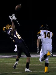 Wylie wide receiver Evan Cantrell picks up a long pass despite being covered by Snyder defensive back Nathan Kendrick during Friday's game won by the Bulldogs, 27-7.