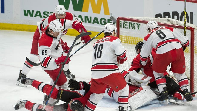 The puck remains in play as bodies from both the Carolina Hurricanes and Ottawa Senators pile up in the third period at the Canadian Tire Centre.