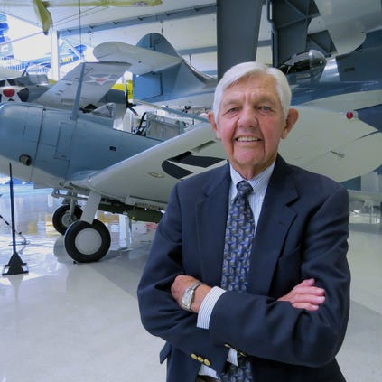 Robert L. Rasmussen,  retiring Director of the National Museum of Naval Aviation.  Behind him is a SBD Dauntless dive bomber, a survivor of the Battle of Midway in World War 2.