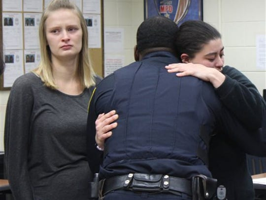 Ashley Fogl, mother of Laylah Petersen, hugs one of the officers who first responded after her daughter was shot in the head, at a Milwaukee police station on Saturday, Nov. 8, 2014. Petersen died Thursday after being shot sitting on her grandfather's lap. At left is Laylah's aunt, Amanda Legler. (AP Photo/Carrie Antlfinger)