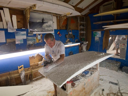 """Charles Williams, founder and maker of Impact Surfboards, shapes a foam board with a Skil 100 planer from his shop Oct. 17, 2017 in Fort Pierce. """"It's all about the shape. You can train monkeys to glass these things and sand them and everything, but the shape, it's all about the shape. That's what counts, that's what rides, that's what makes the boards,"""" Williams said. He mostly works alone and doesn't really advertise, saying marketing is done at the beach when he and others, including twin brother George Williams, use Impact Surfboards. """"I'm a surfer, not a businessman."""""""