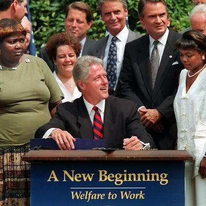 President Bill Clinton, surrounded by former welfare