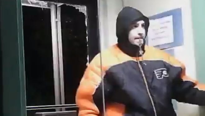 A screen capture from surveillance video of an individual entering Garten Services.